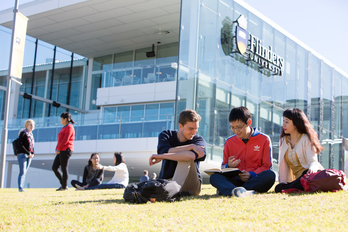 Image of Flinders University with students sitting outdoors in the sunshine