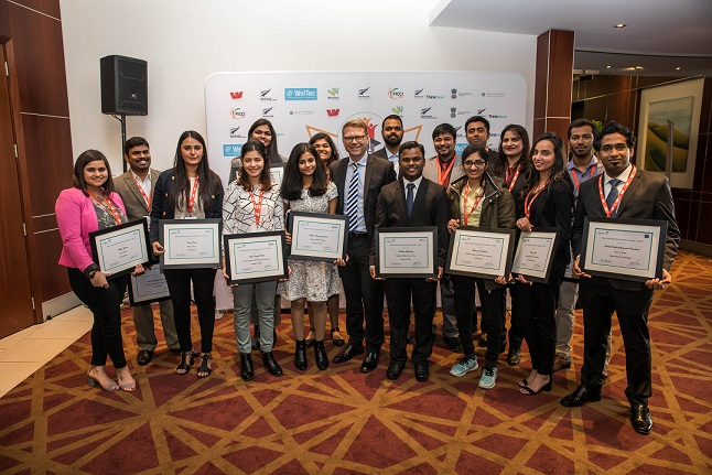 2017 New Zealand excellence awards winners from India, standing and smiling, and holding their award citations