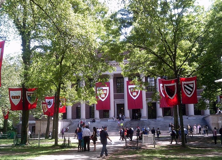 Harvard campus with red banners hanging from green trees for graduation, and people walking about