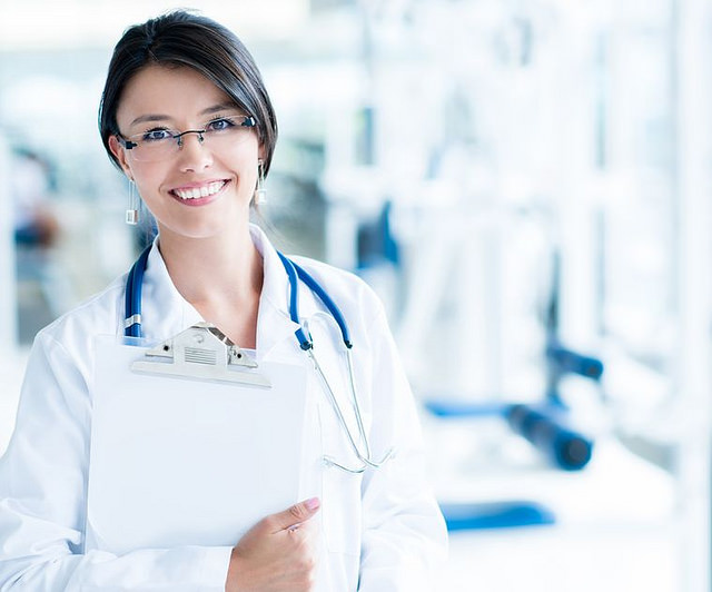 Smiling woman wearing glasses, stethoscope, and white lab coat, holding a clipboard