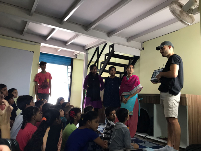 University of Southampton student Joe Rowland (extreme right) teaches school children at Dharavi Diary, Mumbai, how to use a BluPoint device, which lets them access learning resources even without the internet